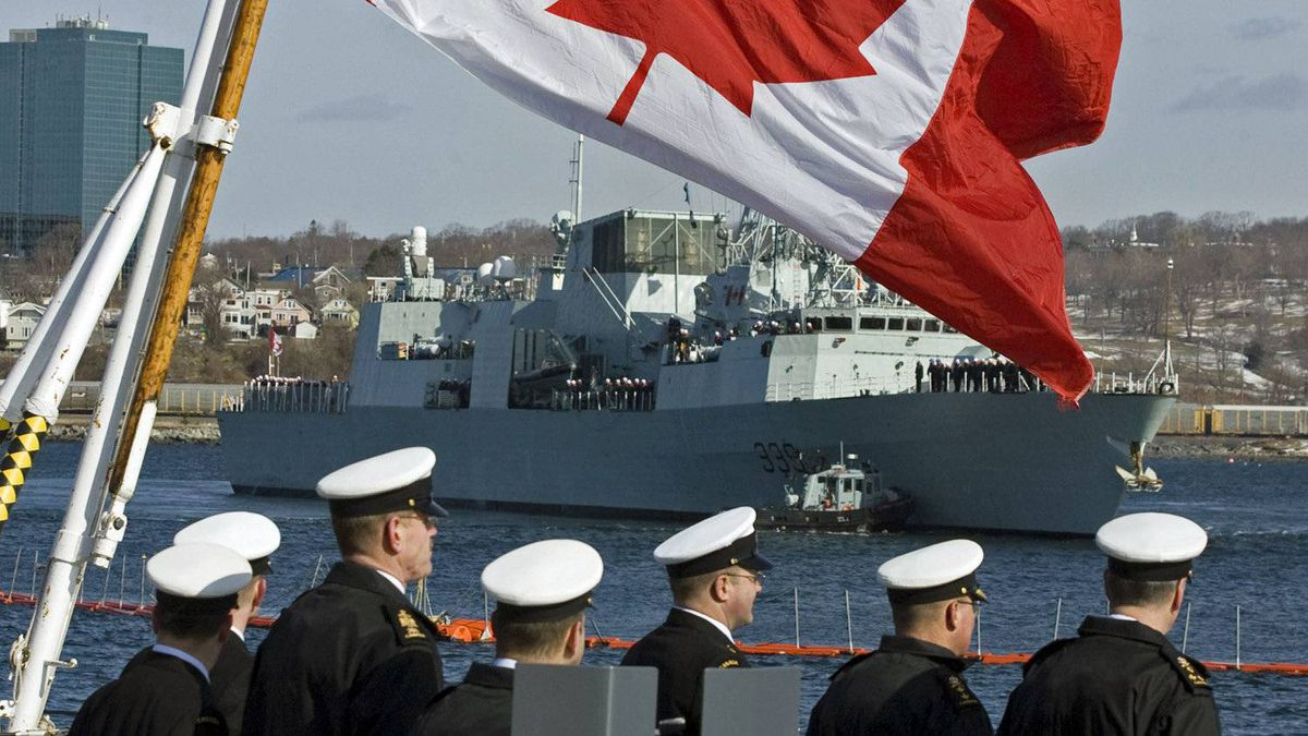 Sailors look on as HMCS Charlottetown heads out to sea in Halifax on March 2, 2011.