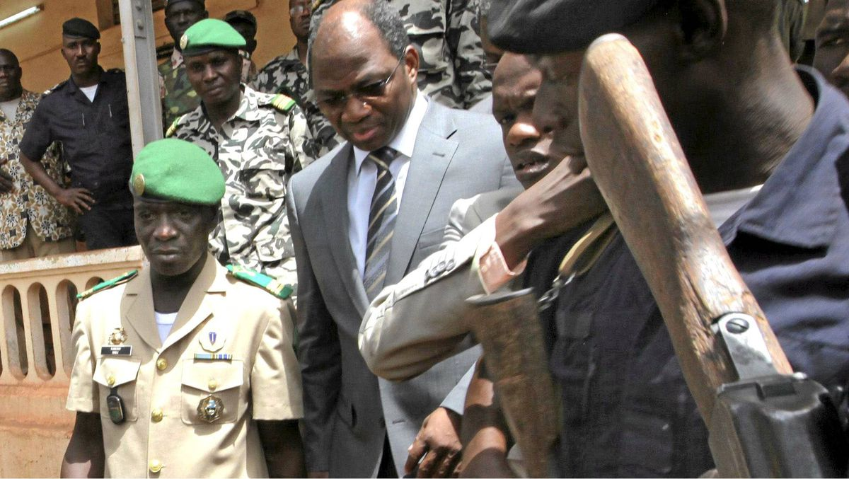 Mali's junta leader Captain Amadou Sanogo, left, arrives with Burkina Faso's foreign affairs minister Djibril Bassole to attend a news conference in Kati, outside Mali's capital Bamako, April 1, 2012.