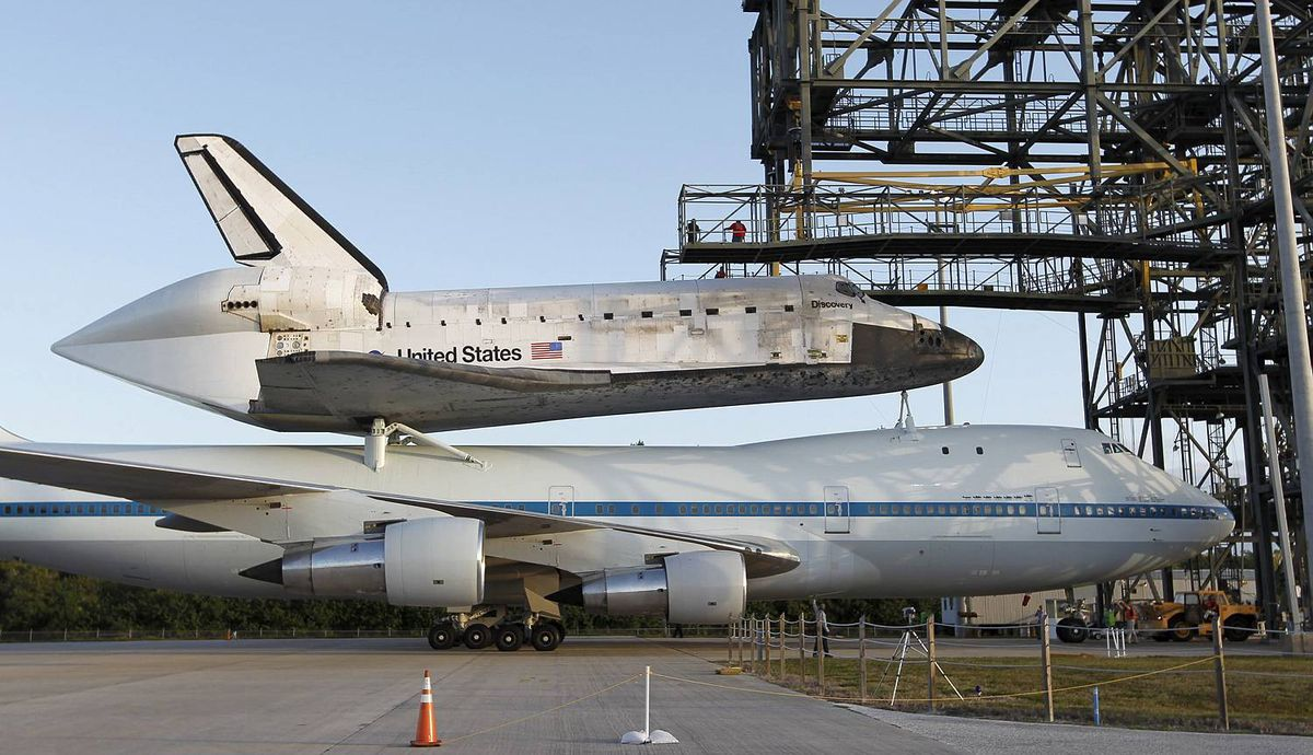 Space shuttle Discovery is shown attached to a modified NASA 747 aircraft at Kennedy Space Center in Cape Canaveral