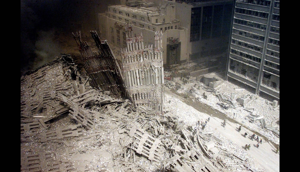 A group of firefighters walk amid rubble near the base of the destroyed South World Trade Center in New York on September 11, 2001.