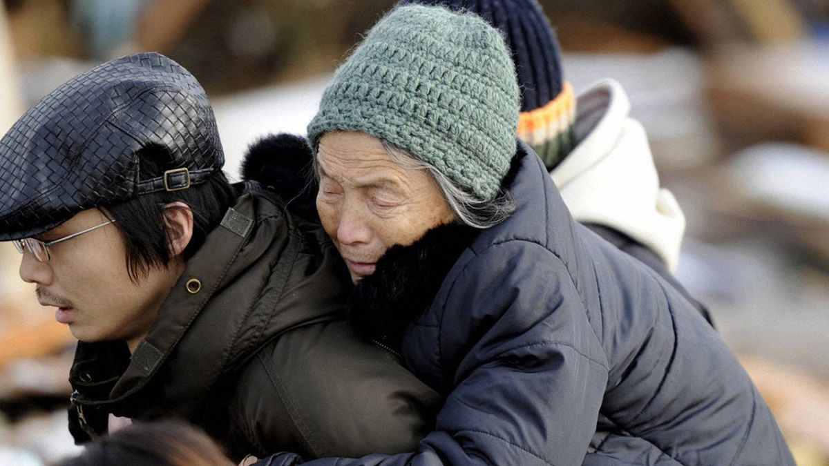 A man carries an elderly woman on his back after a tsunami and earthquake in Sendai, northeastern Japan March 12, 2011.