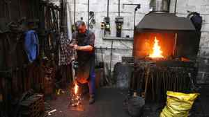 Peter Trick strikes a heated clapper in orger to make it shorter works at the Whitechapel Bell Foundry.