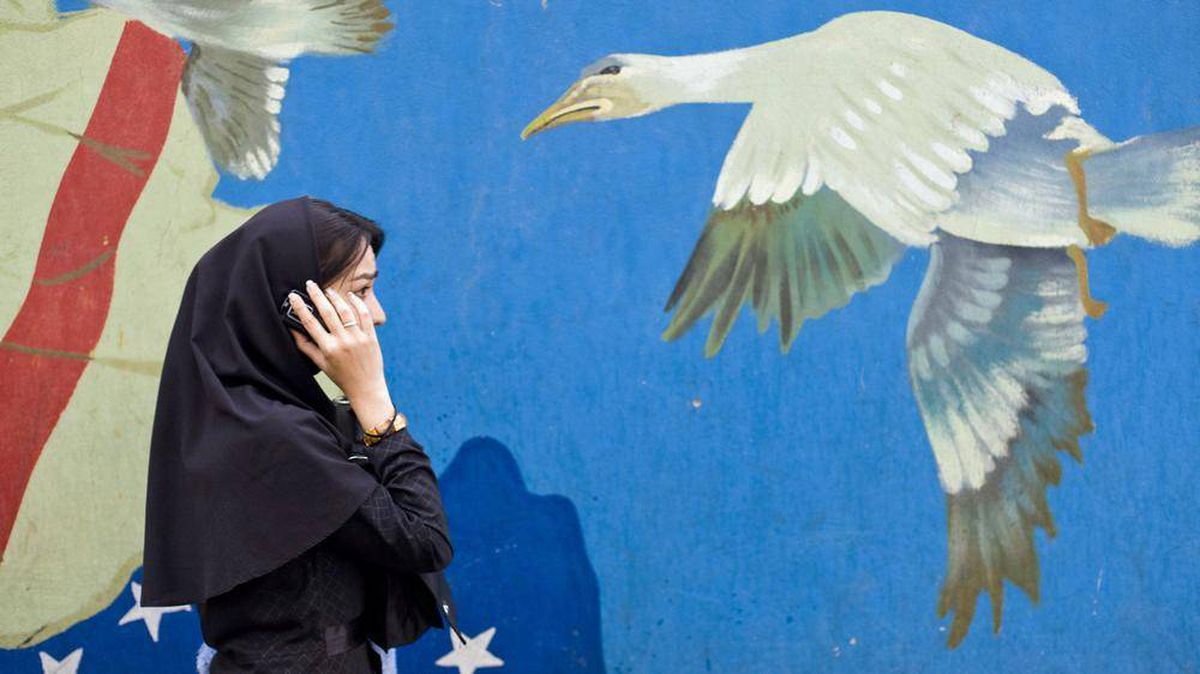 A Iranian woman talks on her mobile phone while passing the former U.S. embassy in Tehran in November of 2008.