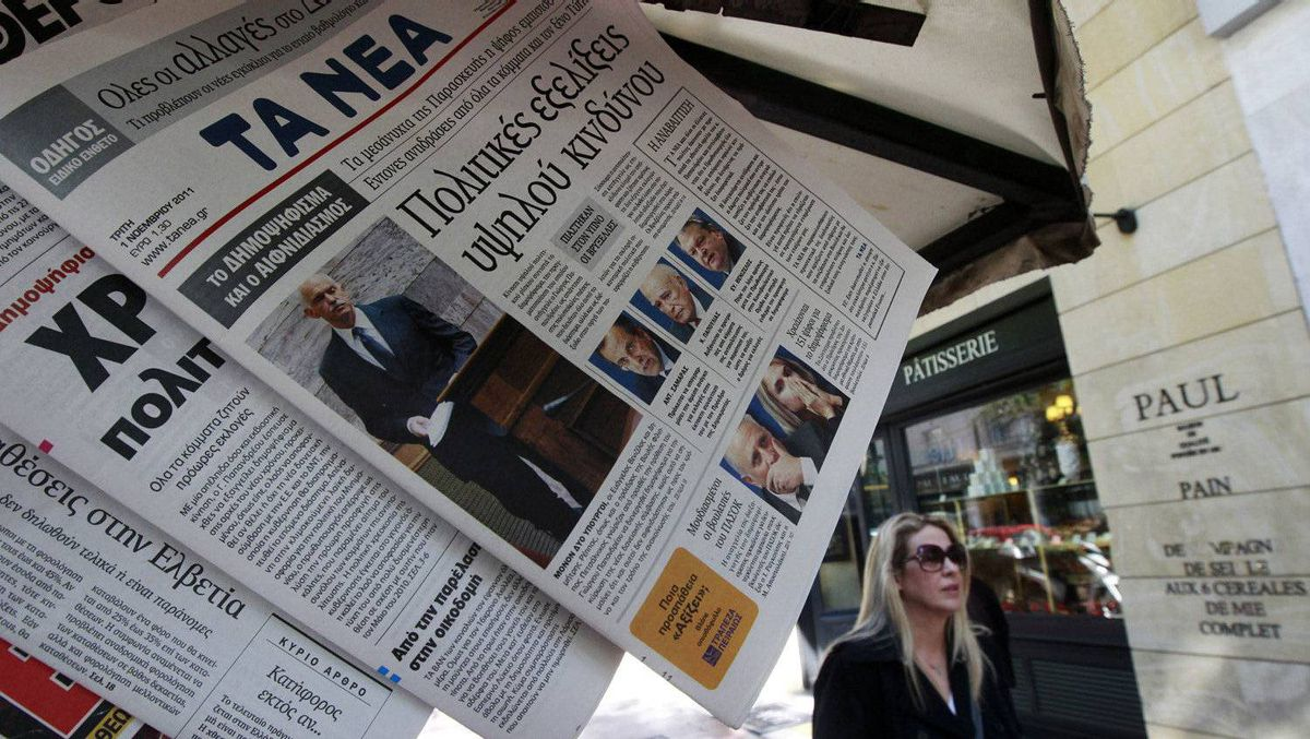 A woman walks past Greek newspapers bearing cover photos of Greek Premier George Papandreou in Athens November 1, 2011.