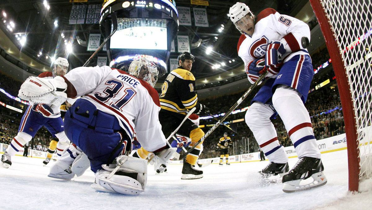 In this photo taken with a fisheye lens, Montreal Canadiens defenseman Brent Sopel, right, knocks the puck out of the crease as Boston Bruins' Nathan Horton and goaltender Carey Price (31) look on during the second period The Habs won 3-1. (AP Photo/Winslow Townson)