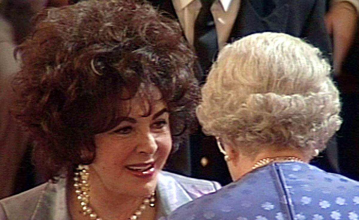 Elizabeth Taylor receives her award as Dame Commander of The Most Excellent Order of the British Empire from the Queen in the ballroom of Buckingham Palace, May 16, 2000. Taylor recieved her award in recognition for her services to acting and charity.