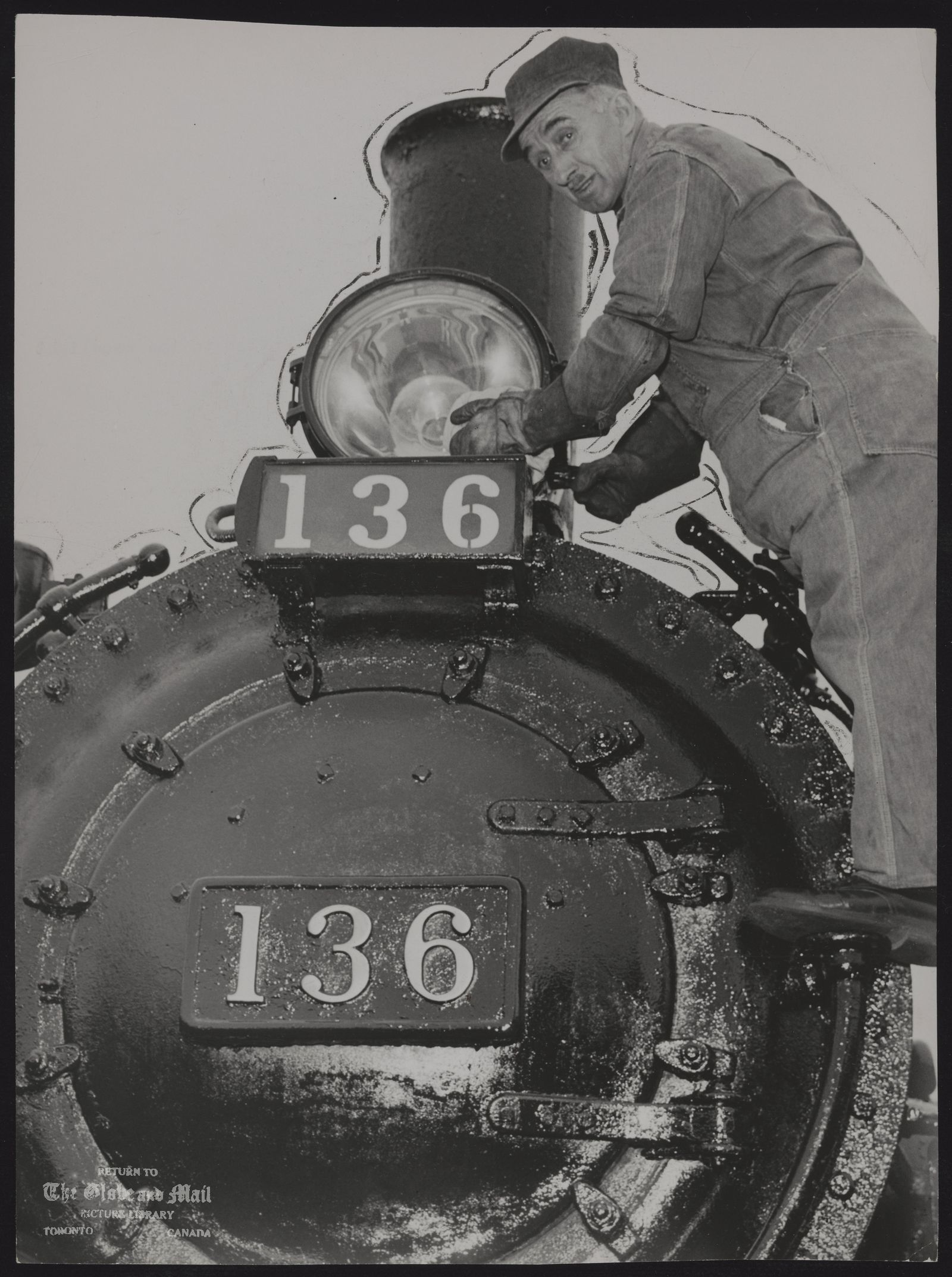 CPR Rolling Stock Hostler Benjamin Jones pays special attention to the headlight on old Engine 136. [NB: Canadian Pacific 136 is a class A-2-m 4-4-0 steam locomotive built in 1883 by the Rogers Locomotive Works for the Canadian Pacific Railway as No. 140. The locomotive was used for both passenger and freight service for the Canadian Pacific railroad. In 1912 she was renumbered to 115, and the following year she was given her final number and reclassified to A2m. No. 136 was retired from the Canadian Pacific roster in 1960. The engine now remains in operating condition at the South Simcoe Railway in Tottenham, Ontario.]