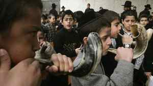 Ultra-Orthodox Jewish youths blow on rams' horns during prayer in Jerusalem.