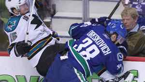 Vancouver Canucks' Victor Oreskovich takes out San Jose Sharks' Dany Heatley during the first period. THE CANADIAN PRESS/Jonathan Hayward