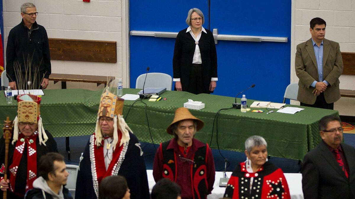 Panel members stand with Haisla First Nation hereditary chiefs during the opening day of hearings for the Northern Gateway project in Kitamaat Village, B.C., on Jan. 10.