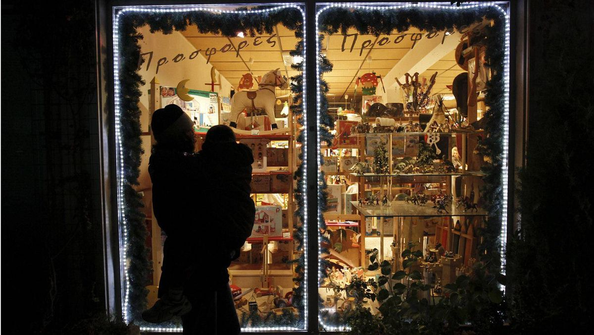 A woman and child take in the window display of the Come and See toy shop in the Athens suburb of Glyfada. Austerity measures in Greece could dampen retail sales.