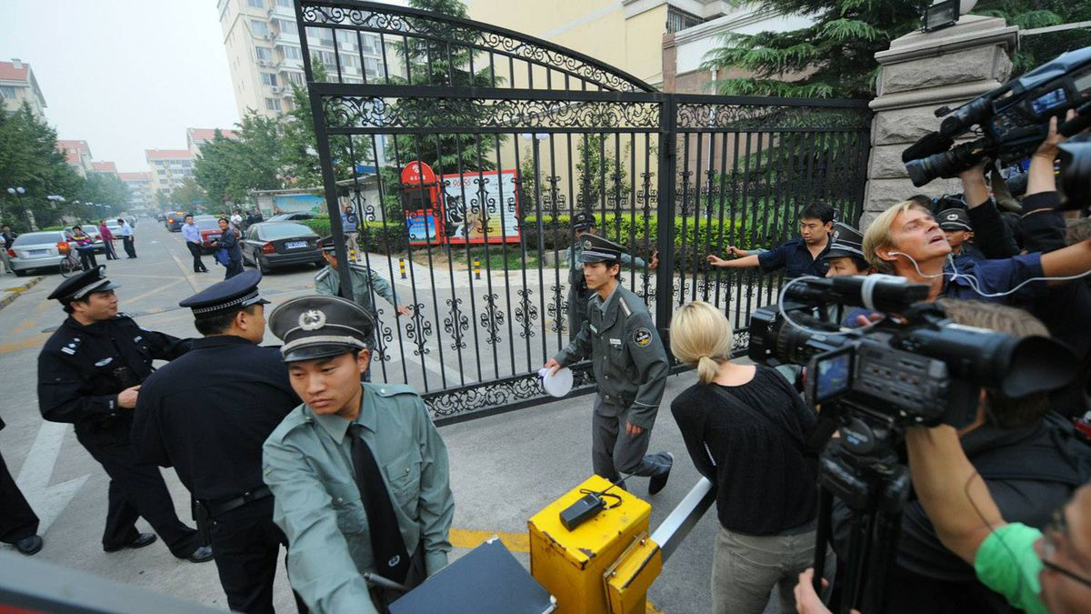 """Chinese policemen close the gate to the apartment compound where jailed dissident Liu Xiaobo home is located, in Beijing on October 8, 2010. China said that the Norwegian Nobel committee has """"violated"""" the integrity of the Peace Prize by awarding it to jailed dissident Liu Xiaobo and warned that ties with Oslo would suffer."""
