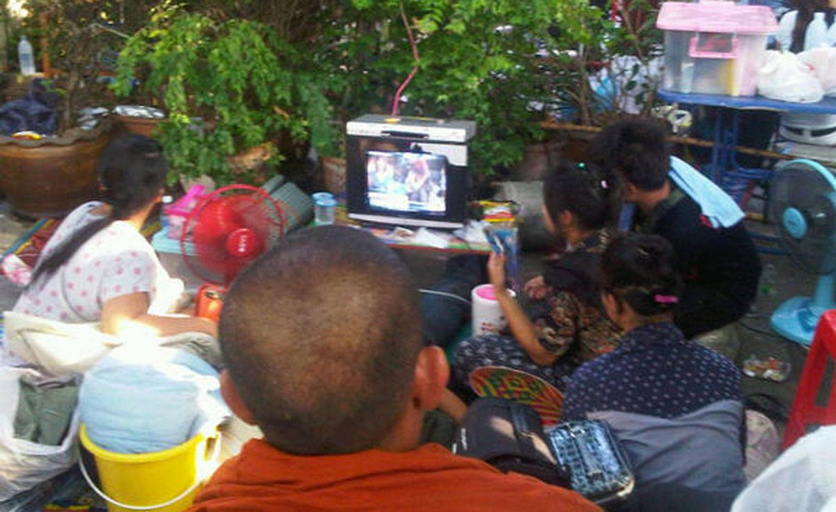 Thais in temple watch on TV as army approaches.
