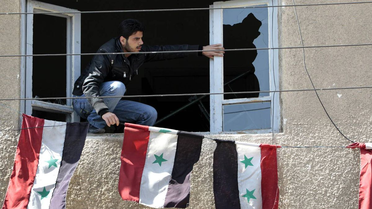 """A Syrian security man, sets Syrian flags through a broken window of the anti-drug police office that was destroyed by Syrian anti-government protesters, in the southern city of Daraa, Syria, Monday March 21, 2011. Mourners chanting """"No more fear!"""" have marched through a Syrian city where anti-government protesters had deadly confrontations with security forces in recent days. The violence in Daraa, a city of about 300,000 near the border with Jordan, was fast becoming a major challenge for President Bashar Assad, who tried to contain the situation by freeing detainees and promising to fire officials responsible for the violence."""