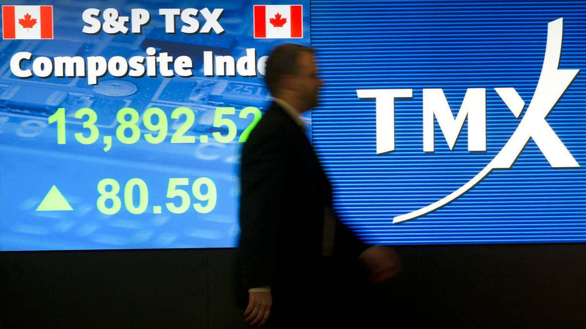An employee passes a stock board at the Toronto Stock Exchange.