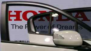 Logo of Honda Motor Co is seen through car doors at the company showroom in Tokyo April 27, 2012.