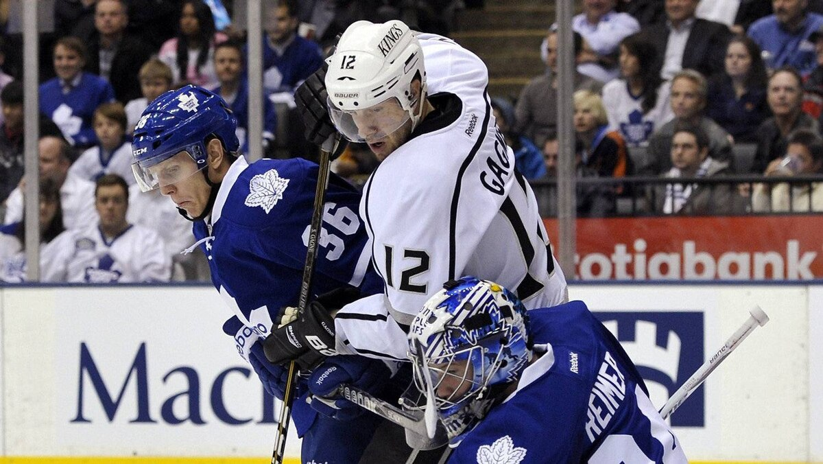 Toronto Maple Leafs goalie James Reimer (R) kicks the puck away from defenceman Carl Gunnarsson (L) and Los Angeles Kings forward Simon Gagne during the first period of their NHL hockey game in Toronto December 19, 2011.