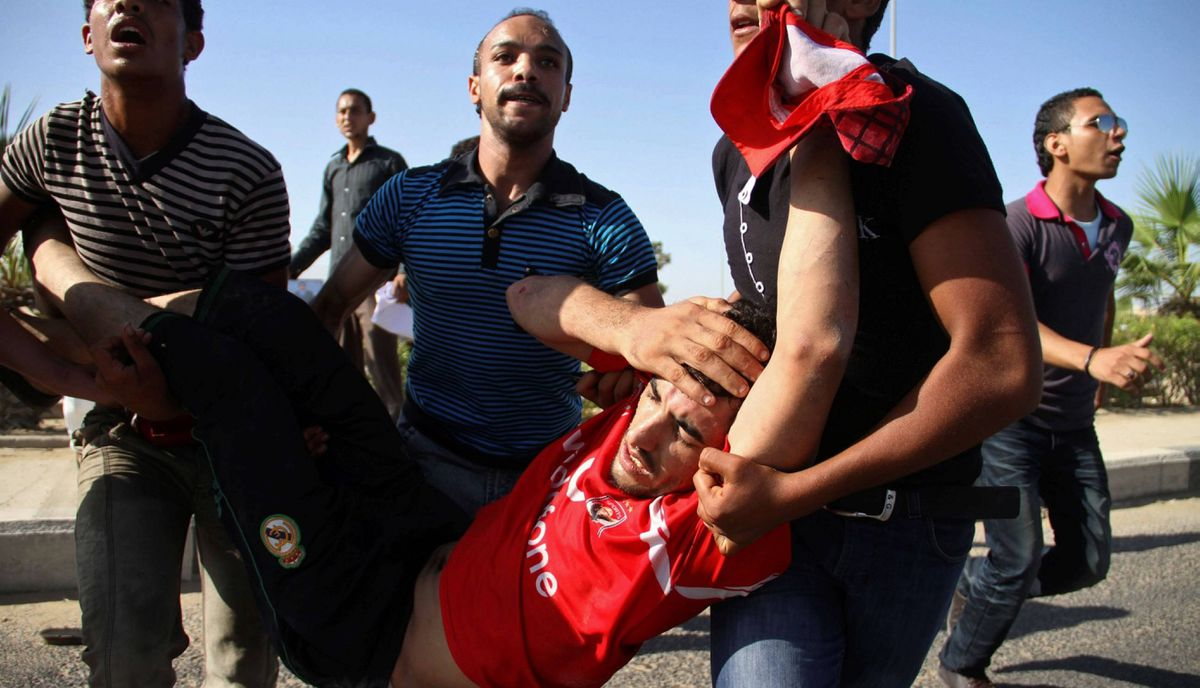 An injured man is carried away during clashes between supporters of Egypt's ousted President Hosni Mubarak and anti-Mubarak protesters outside a police academy.