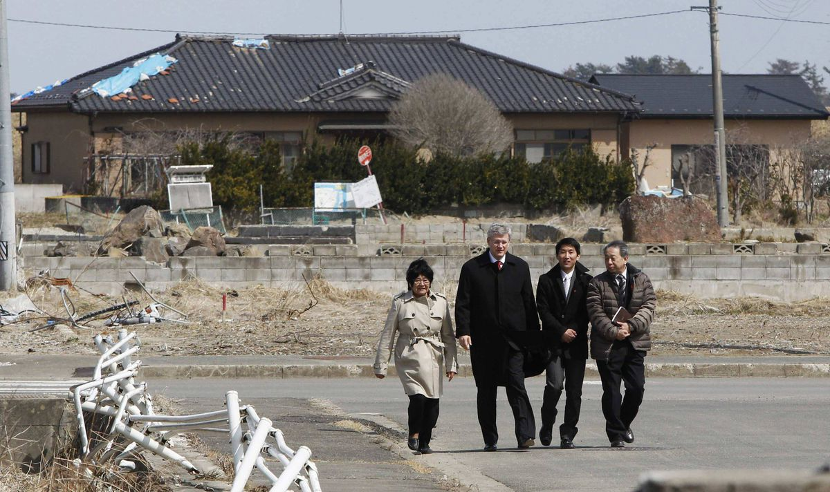 Canadian Prime Minister Stephen Harper (2nd L) walks with Yuriage Junior High School Principal Sumio Takahashi (R), Canada's International Co-operation Minister, Bev Oda (L), and an unidentified official, as he visits a school, which had an area damaged by the March 11, 2011 earthquake and tsunami, in Natori, Miyagi prefecture, March 26, 2012.