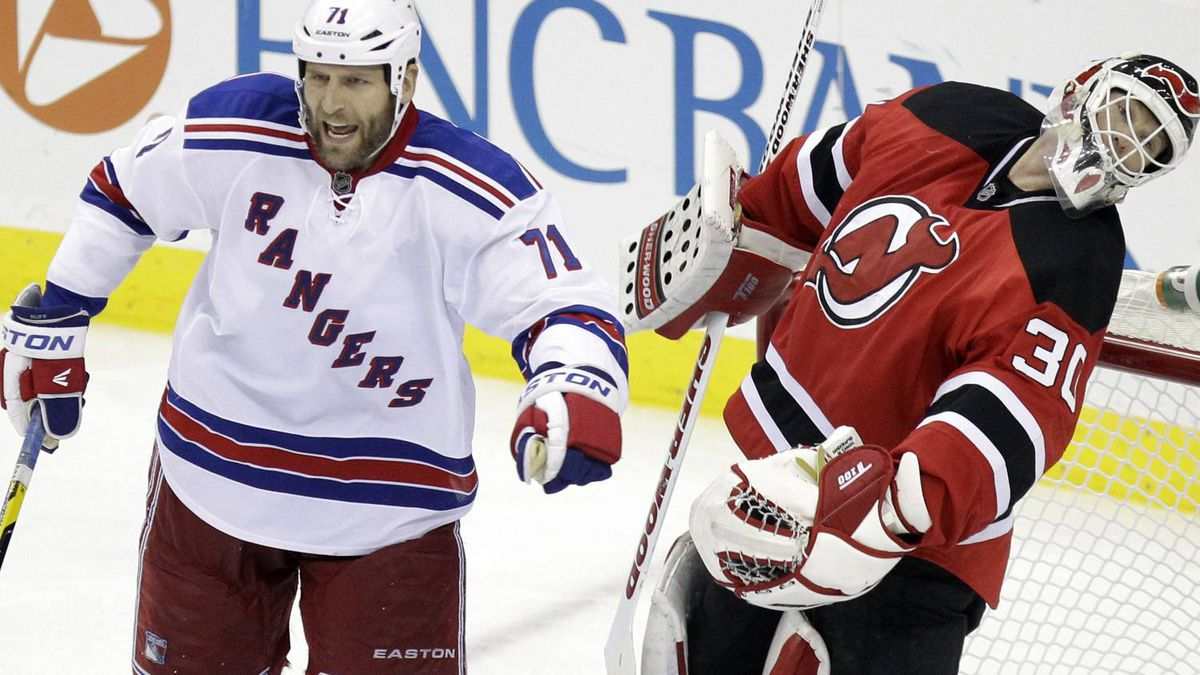 New Jersey Devils goalie Martin Brodeur reacts after being punched by New York Rangers' Mike Rupp, center, during the third period of Game 4 of an NHL hockey Stanley Cup Eastern Conference final playoff series, Monday, May 21, 2012, in Newark, N.J. The Devils won 4-1. (AP Photo/Julio Cortez)