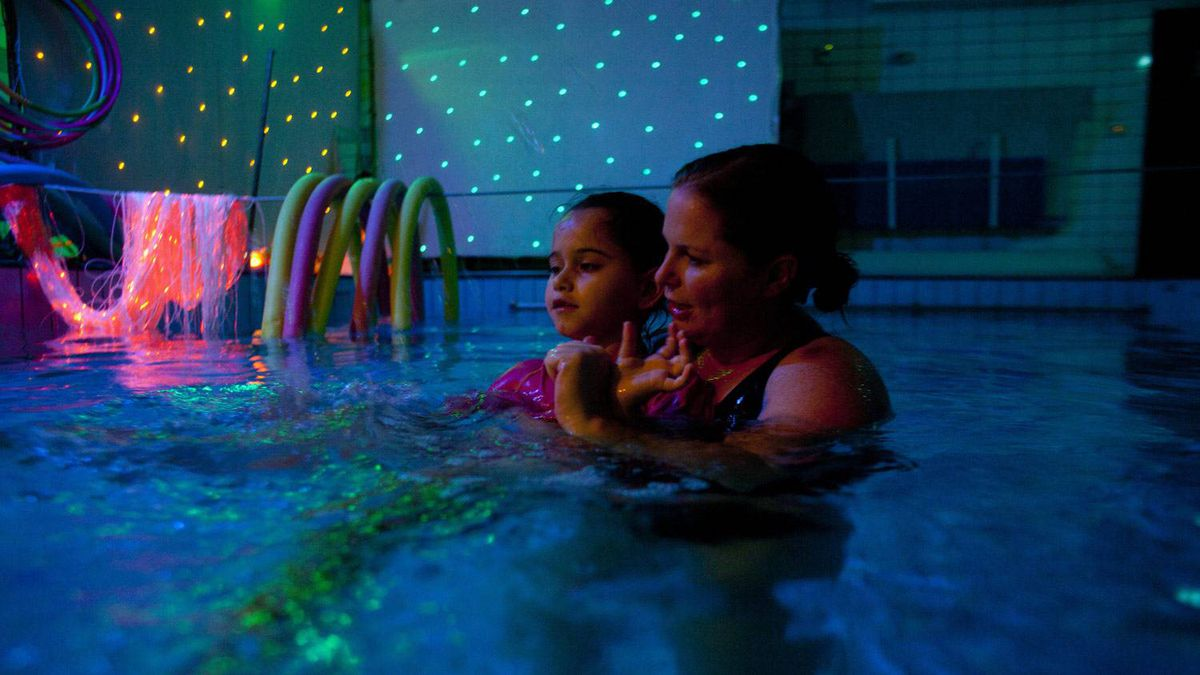 Ms. Yoshei, a hydrotherapist, uses lights together with water as she treats an autistic child in a swimming pool. She leaves work at 3:30 to pick up her girls and be with them at home.