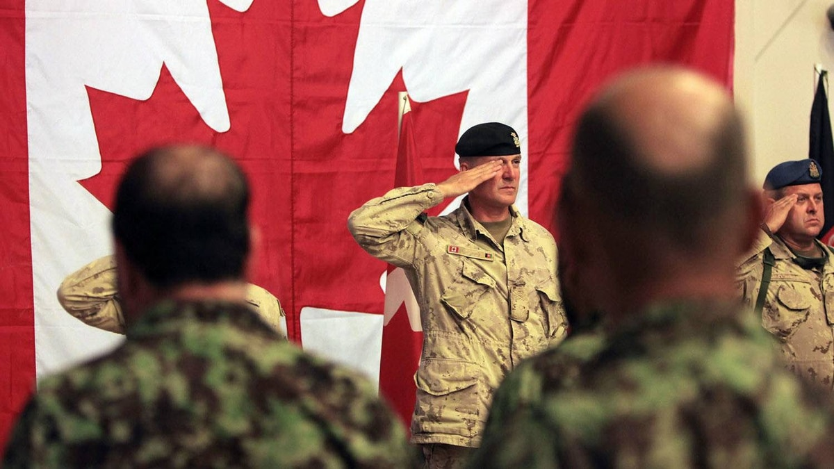 Brig.-Gen Dean Milner center, Commander of Canadian Forces Kandahar slaute along with others for Afghan and Canadian anthem during a transfer of command authority ceremony in Kandahar airbase in Afghanistan, Thursday, July 7, 2011.