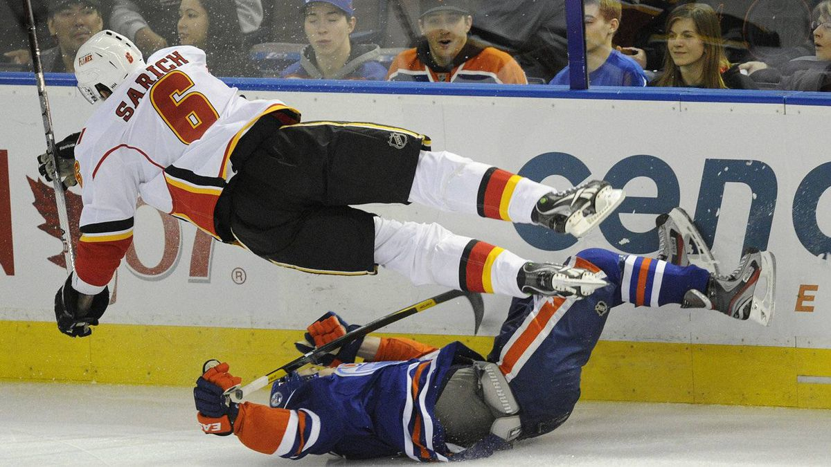 Calgary Flames' Cory Sarich, top, crashes into the Edmonton Oilers' Taylor Hall during first period NHL hockey game action in Edmonton on Friday, March 16, 2012. Sarich signed a 5-year contract with Calgary worth 3.6-million dollars a year in 2008.