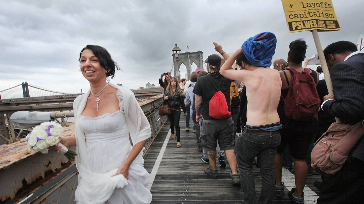 A bride walks past demonstrators affiliated with the Occupy Wall Street movement as they cross the Brooklyn Bridge walkway on October 1, 2011 in New York City.