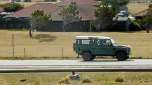 A vehicle drives past British military housing where Prince William is living, top, in Mount Pleasant, Falkland Islands.