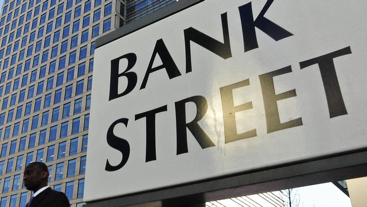 A pedestrian passes a street sign in the Canary Wharf financial district, in east London March 7, 2011.