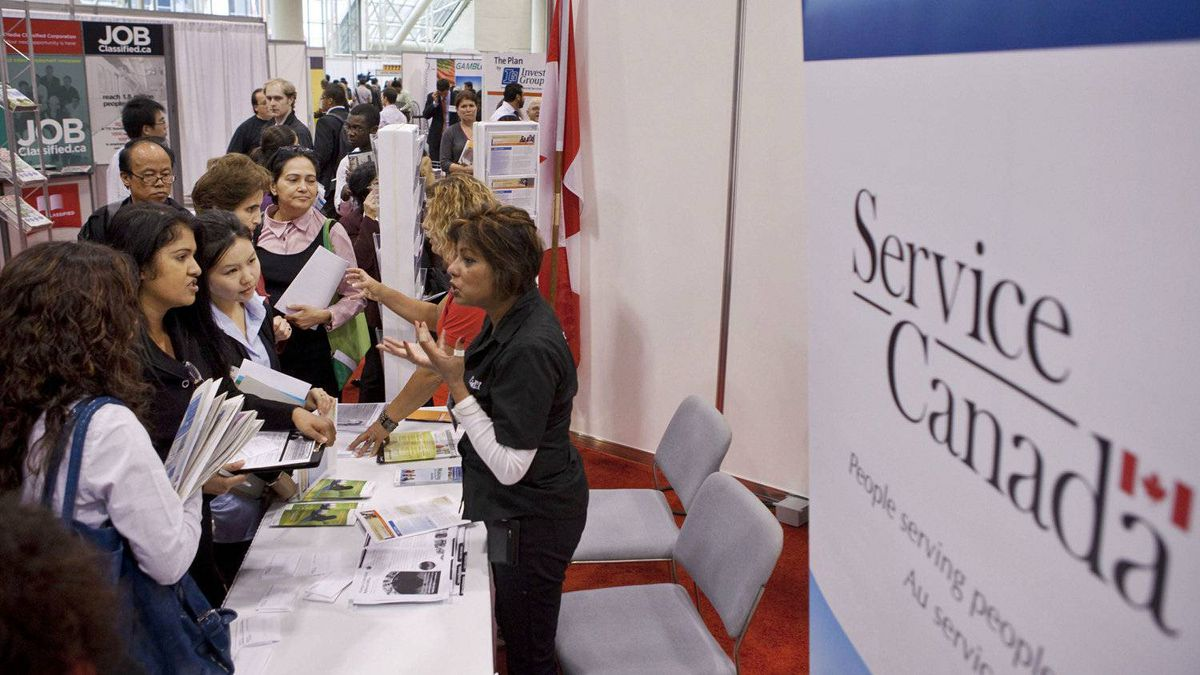 Job seekers speak with personnel at the Service Canada kiosk during the 19th edition of the National Job Fair and Training Expo at the Metro Toronto Convention Centre on Tuesday, Sept. 27, 2011.