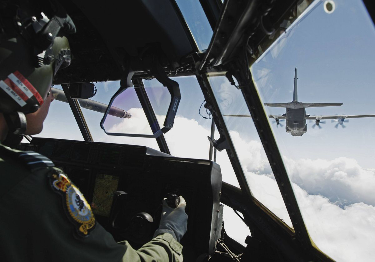 Co-pilot Flight Lieutenant Matt Compton flies an RAF C130 Hercules during a fixed wing aircraft rehearsal for a flypast for the forthcoming Diamond Jubilee celebrations for Britain's Queen Elizabeth after taking off from RAF Brize Norton in southern England May 15, 2012.