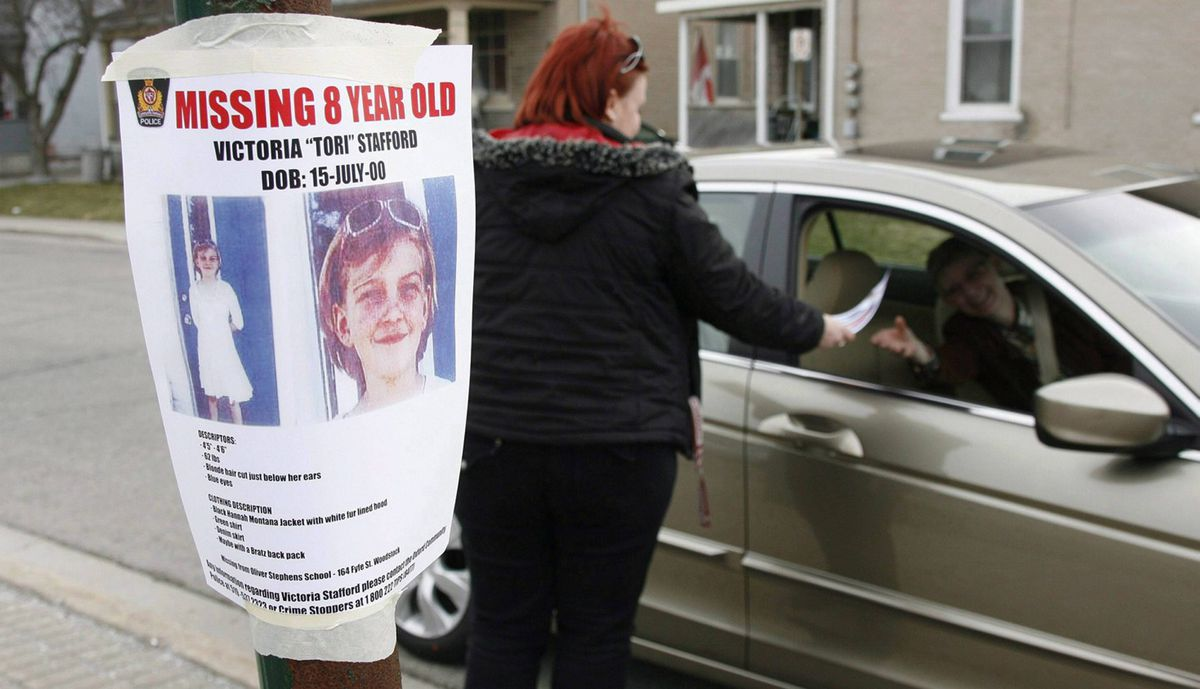 """Tiffany Ackers hands out a poster for then-missing Victoria """"Tori"""" Stafford, 8, on a street corner in Woodstock, Ont. on Friday April 10, 2009."""