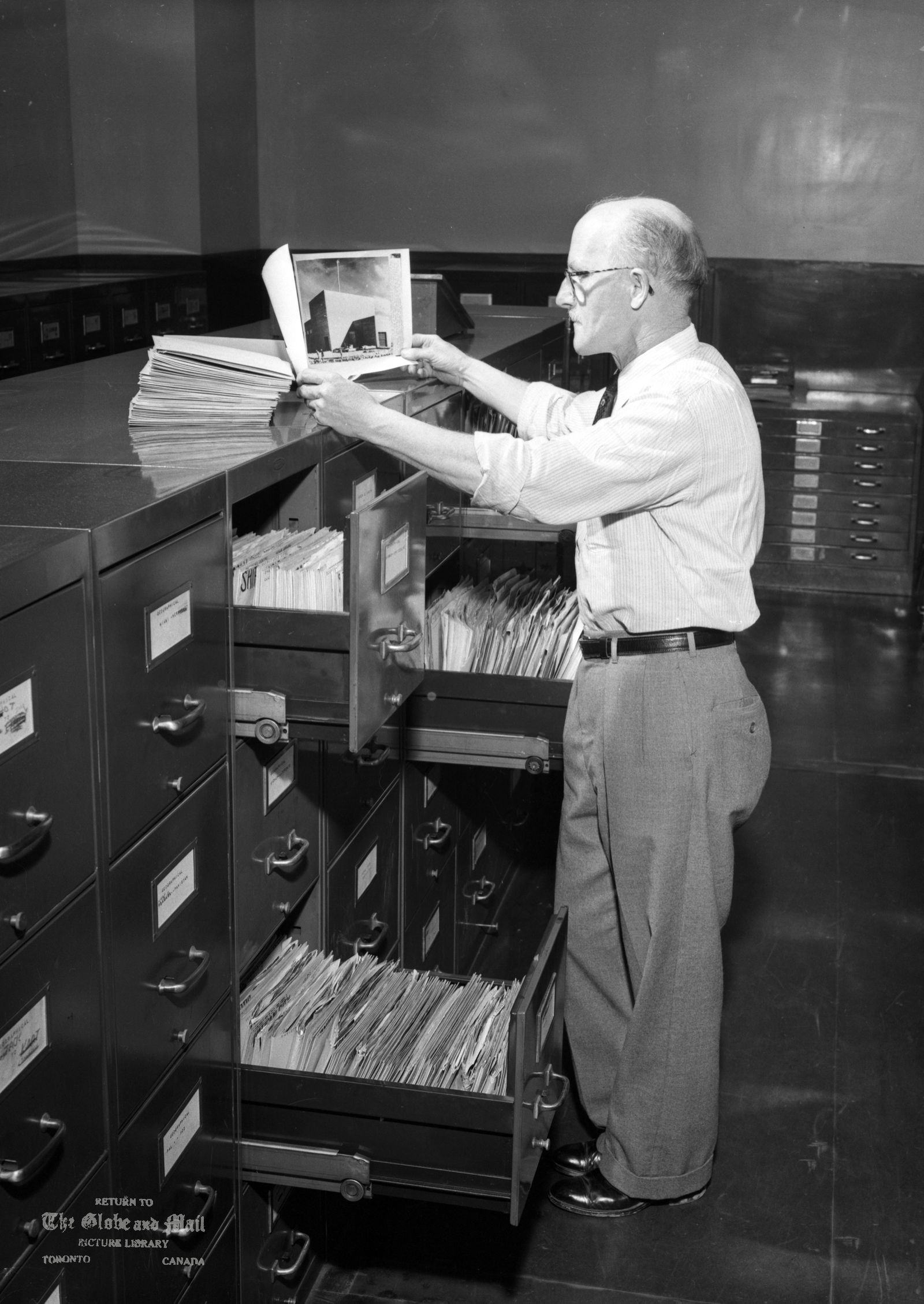 Globe and Mail Library Clerk by Photo Cabinets, 1957. Credit: The Globe and Mail.