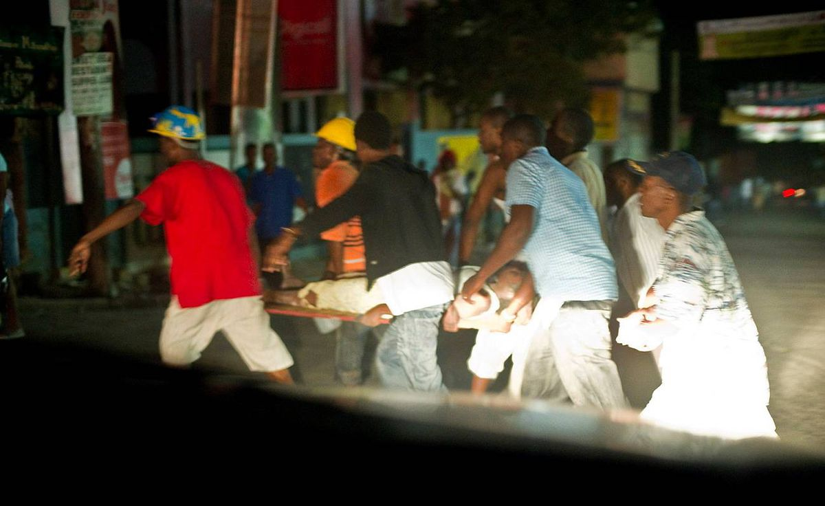 A wounded person is carried on a stretcher after a major earthquake on January 12, 2010 in Port-au-Prince, Haiti. A 7.0 earthquake rocked Haiti, followed by at least a dozen aftershocks, causing widespread devastation in the capital of Port-au-Prince.