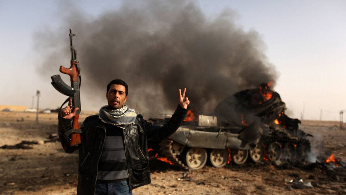 A Libyan rebel flashes a V-sign in front of burning tank belonging to loyalist forces bombed by coalition air force in the town of Ajdabiya on March 26, 2011 as forces loyal to Libyan leader Moamer Kadhafi were retreating after rebels recaptured the key eastern town in their first significant victory since the launch of the Western-led air strikes a week ago.