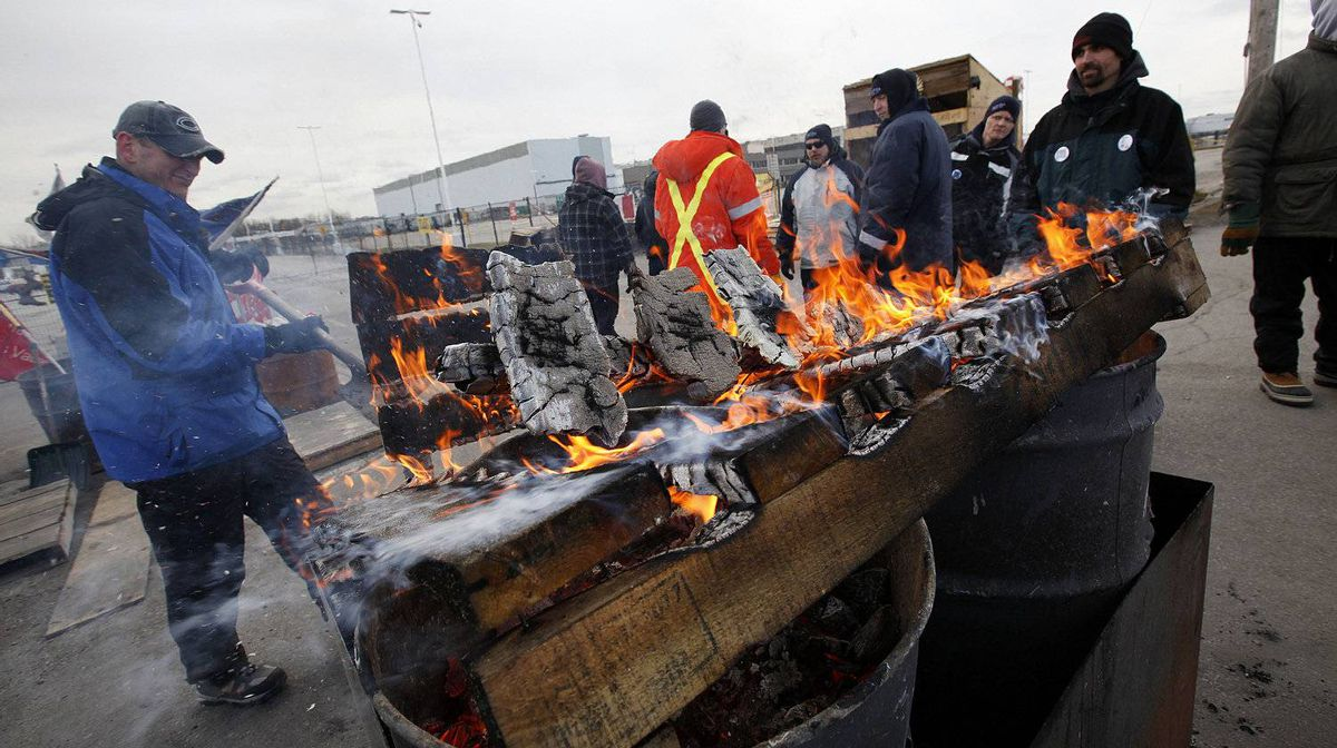 Electro-Motive Canada employees burn pallets to keep warm on the picket line outside the subsidiary of Caterpillar in London on Feb. 8, 2012.