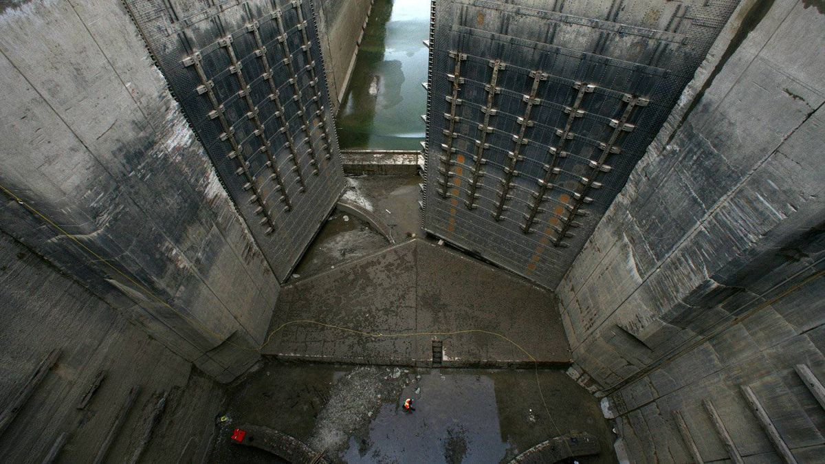 A man walks along the bottom of the drained passageway between locks #4 and #5. These doors, the largest, are 90 feet high.