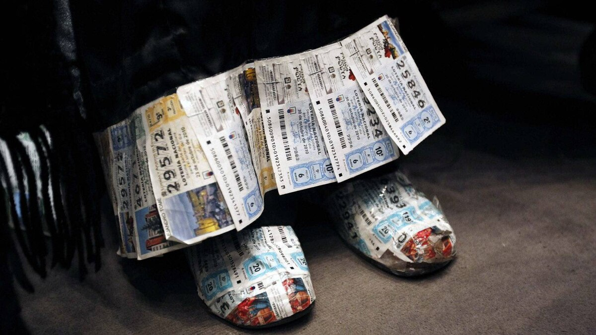 Old lottery tickets adorn a woman's shoes and the hem of her dress at the drawing of 'El Gordo,' Spain's multibillion-euro Christmas lottery.