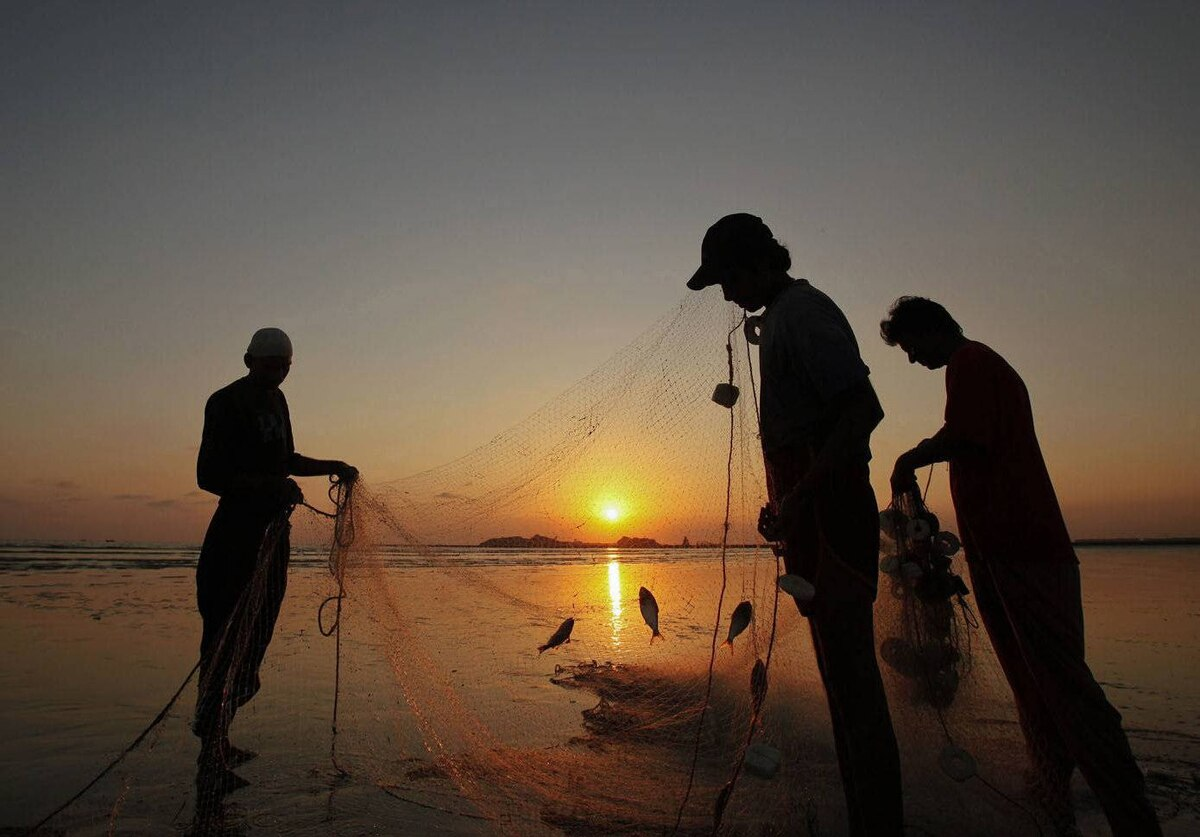 Fishermen are silhouetted against the setting sun as they clear their net after fishing at Clifton beach in Karachi, Pakistan.