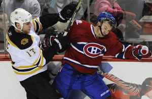 Boston Bruins' Milan Lucic checks Montreal Canadiens' Josh Gorges during third period NHL hockey action in Montreal, Feb. 7, 2010.