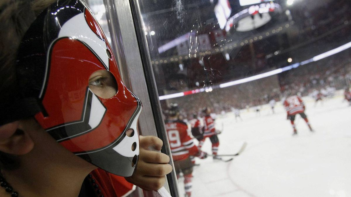 A.J. Micaliezi from Middletown, New Jersey, wears a hockey mask as he watches warm ups ahead of Game 1 of the Stanley Cup final between the Los Angeles Kings and the New Jersey Devils in Newark, New Jersey, May 30, 2012.