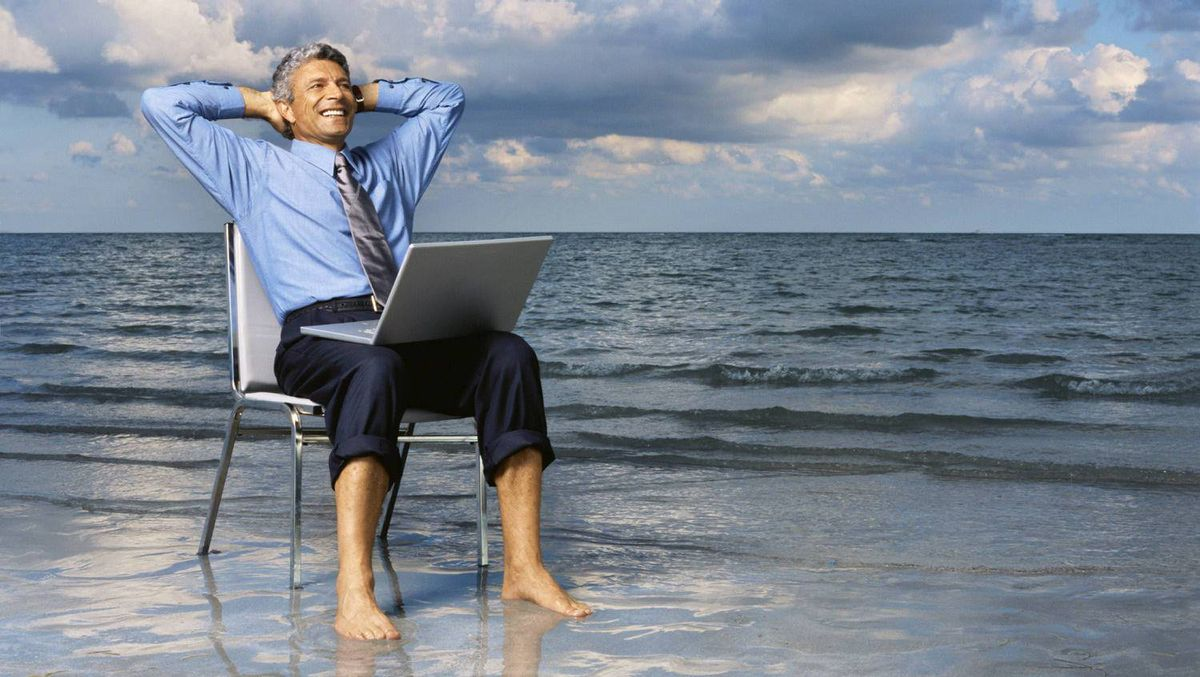 Businessman sitting on a chair on the beach with his hands behind his head.