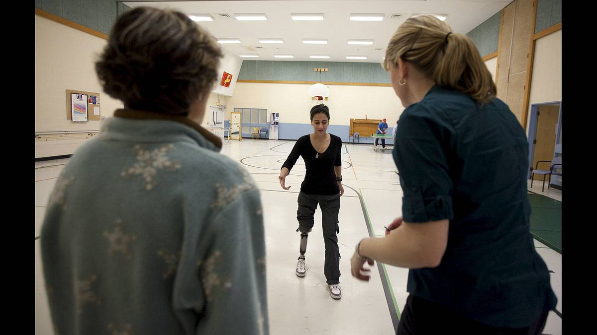 Bushra Saeed works with her prosthetist Laura Scholtes, right, and physiotherapist Marie Andree Paquin at the Rehabilitation Centre in Ottawa.
