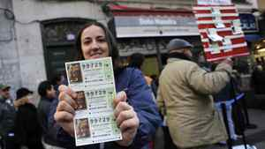 A young woman holds lottery tickets in front of the famous lottery shop Dona Manolita near the Puerta del Sol square in Madrid on Dec. 21, 2011, the evening before the El Gordo draw. Millions of crisis-hit Spaniards snatched up tickets for the world's richest lottery draw, held Thursday, which showered winners with a record $3.3 billion in prizes.