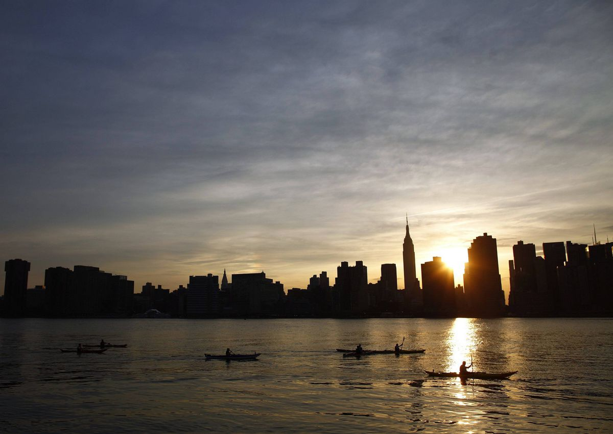 Kayakers paddle in the East River as the Manhattan skyline is seen in New York.