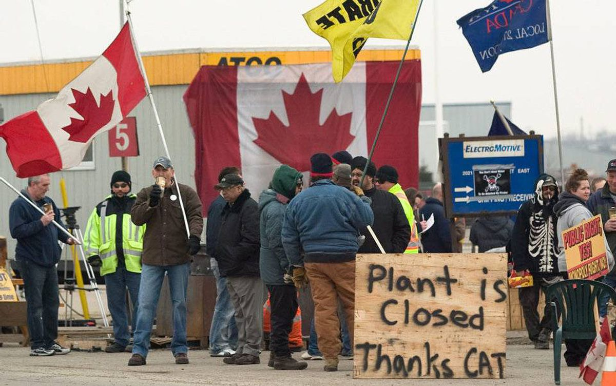CAW workers picket outside at the Electro-Motive plant in London, Ont., on Feb. 3, 2012. American-based heavy equipment maker Caterpillar Inc. announced Friday it was closing the plant, a month after it locked out about 450 workers.