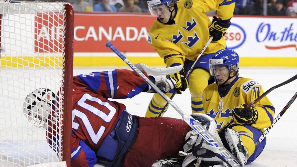 Russia's Andrei Makarov just barely keeps the puck out of the goal as Sweden's William Karlsson, right, and Mika Zibanejad crash the net in the first.
