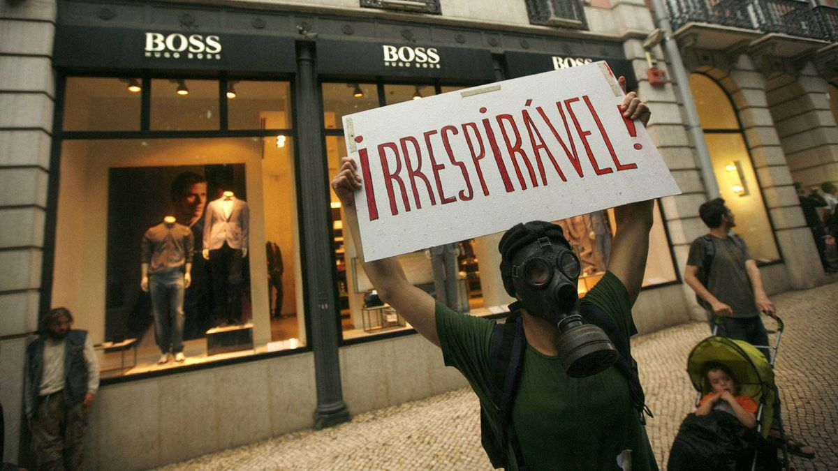 "A demonstrator holds a banner saying ""unbreathable!"" during a protest against politicians, bankers and the authorities' handling of the economic crisis in Lisbon May 28, 2011."