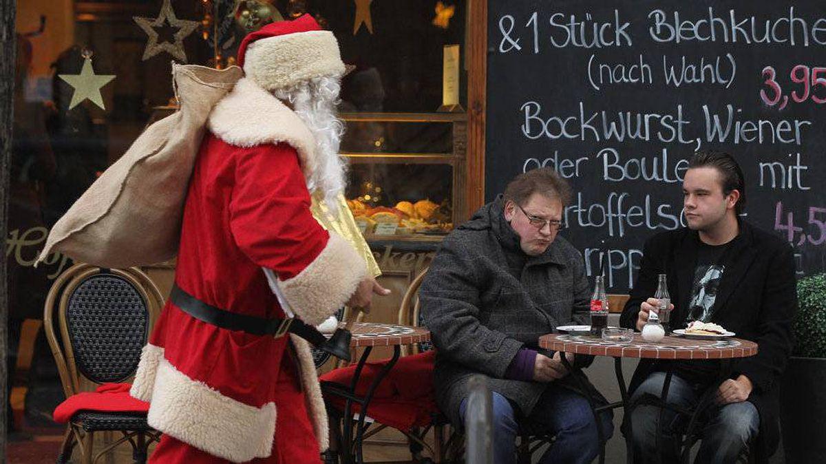 Santa walks past a cafe in Berlin.